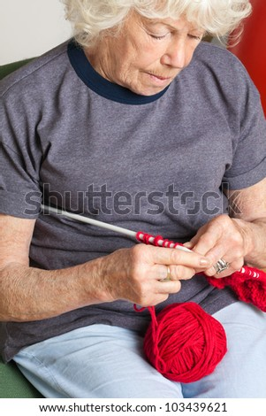 Senior woman using knitting needles with red wool - stock photo