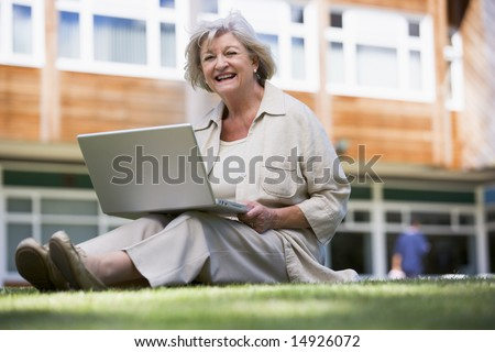 Senior woman using laptop on campus - stock photo
