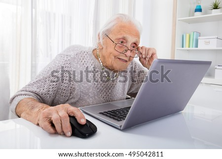 Senior Woman Using Laptop On Desk At Home