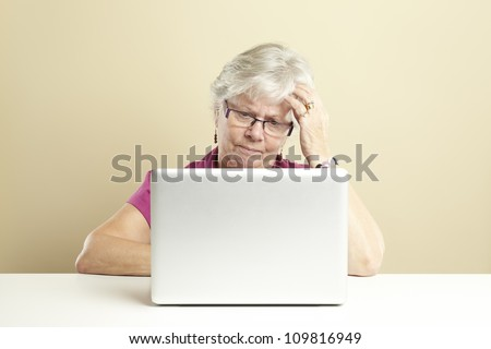 Senior woman using laptop whilst looking confused - stock photo