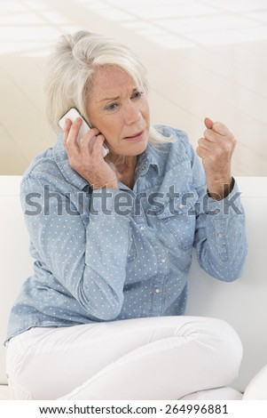 Senior Woman Using Phone At Home seated on sofa - stock photo