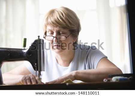 Senior woman using sewing machine at home
