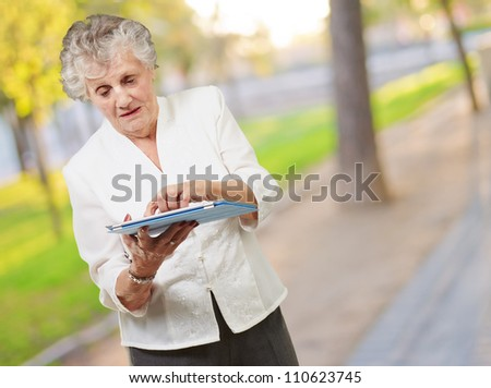 Senior woman using tablet, outdoor - stock photo