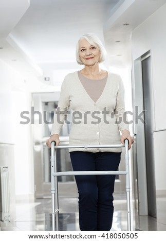 Senior Woman Using Walker At Rehab Center - stock photo