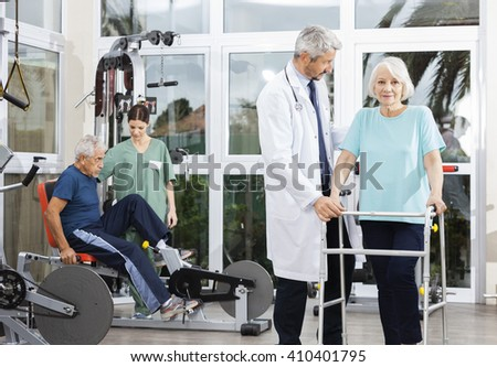Senior Woman Using Walker While Doctor Assisting Her - stock photo