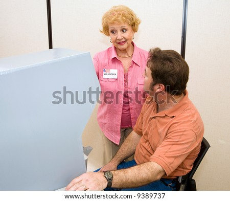 Senior woman volunteer explains the new voting machine to a voter. - stock photo