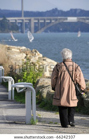 "Senior woman walking along the coast in Le Relecq Kerhuon with the bridges ""Pont Plougastel"" and ""Pont de l'Iroise"" in the background."