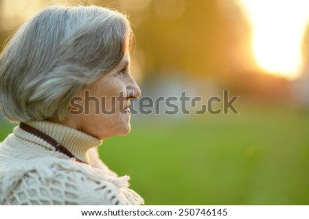 Senior woman walking in autumn park - stock photo