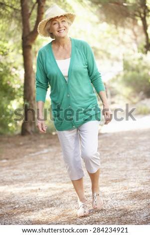 Senior Woman Walking In Countryside - stock photo