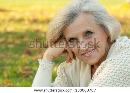 Senior woman walking in the park in autumn - stock photo