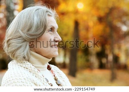 Senior woman walking in the park in autumn - stock photo
