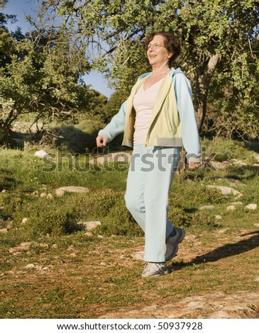 senior woman walking outdoors - stock photo