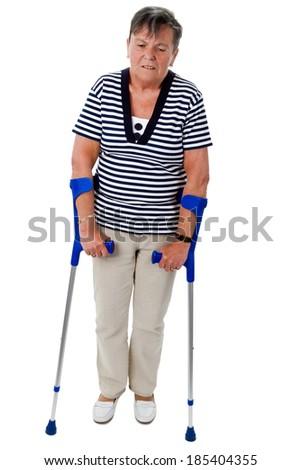 Senior woman walking with crutches - isolated on white - stock photo