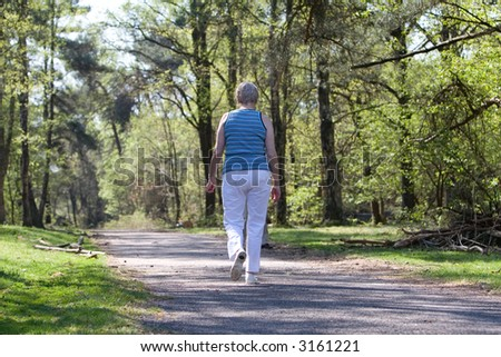Senior woman walking with her back to the camera - stock photo