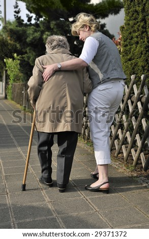 Senior woman walking with the help of a daughter - stock photo