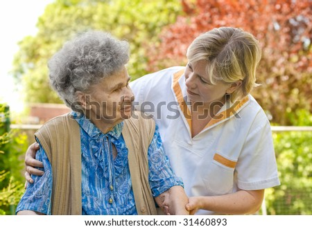 Senior  woman walking with the help of her nurse - stock photo