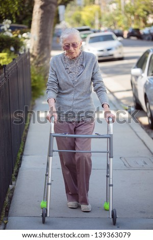 Senior woman walking with walker on street - stock photo