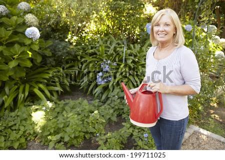 Senior woman watering garden - stock photo