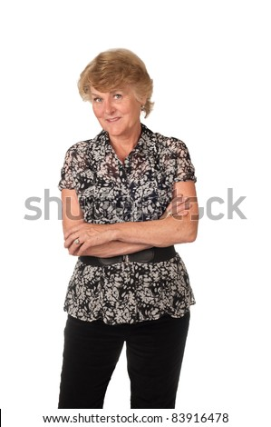 Senior Woman Wearing Black Pants and a Black and White Blouse with Cute Grin on her Face with Arms Folded Isolated on White - stock photo