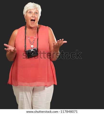 Senior Woman Wearing Camera Shrugging Isolated On Black Background - stock photo