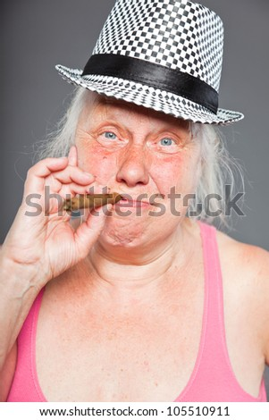 Senior woman wearing hat and smoking cigar. Cool and hip looking. Studio shot isolated on grey background. - stock photo
