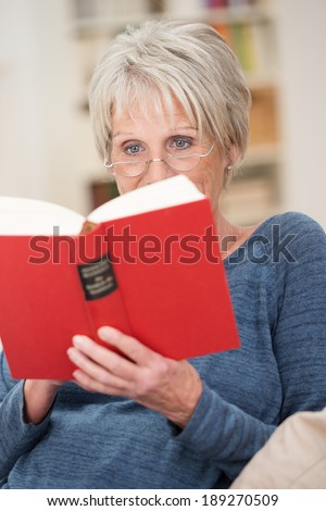 Senior woman wearing reading glasses relaxing with a red hardcover book in a comfortable armchair in her living room - stock photo