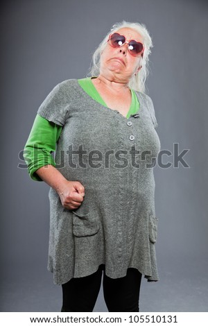 Senior woman wearing sunglasses with expressive face. Funny. Studio shot isolated on grey background. - stock photo