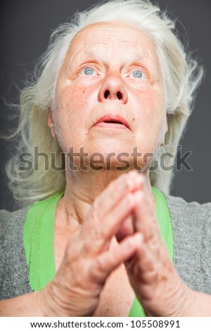 Senior woman white grey hair doing spiritual poses. Expressive face and hands. Studio shot isolated on grey background. - stock photo