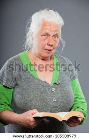 Senior woman white grey hair reading a book. Studio shot isolated on grey background. - stock photo