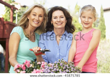 Senior Woman With Adult Daughter And Granddaughter Gardening Together - stock photo