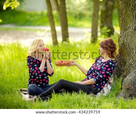 Senior woman with adult daughter in garden - stock photo