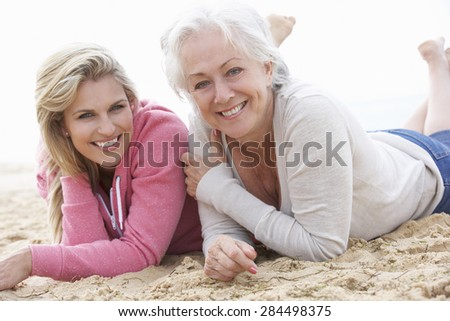 Senior Woman With Adult Daughter Relaxing On Beach - stock photo