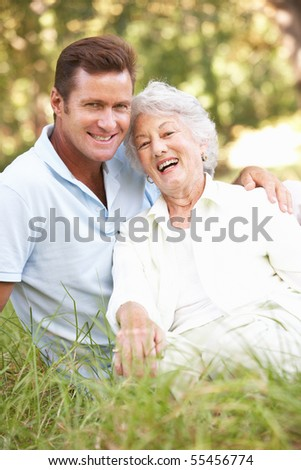 Senior Woman With Adult Son In Garden - stock photo