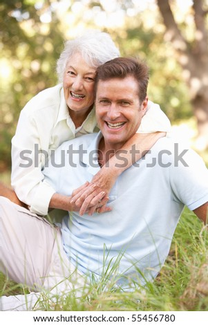 Senior Woman With Adult Son In Garden