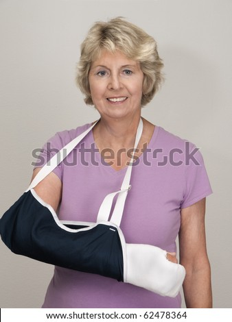 Senior woman with arm in cast and sling after injury or surgery. Gray background. - stock photo