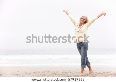 Senior Woman With Arms Outstretched On Winter Beach - stock photo