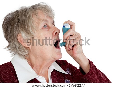 Senior woman with asthma inhaler, isolated on white - stock photo