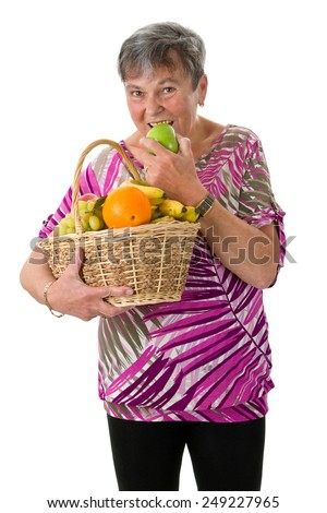 Senior woman with basket of fruit biting into an apple
