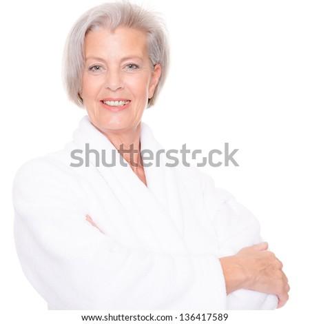 Senior woman with bathrobe in front of white background - stock photo