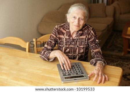 Senior woman with big calculator - stock photo