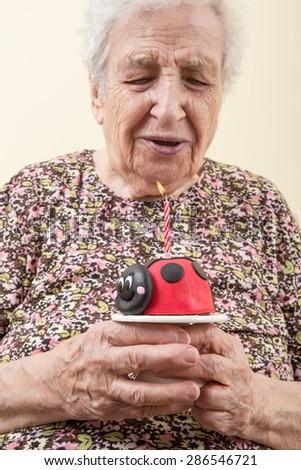 senior woman with birthday cake - stock photo