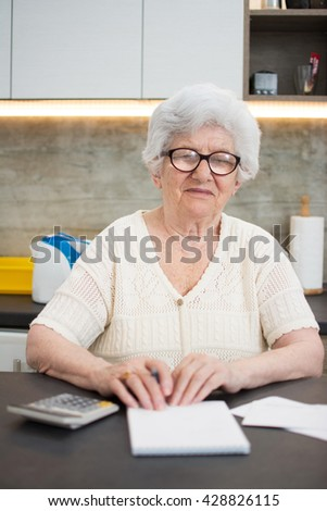 Senior woman with calculator and papers counting at home.