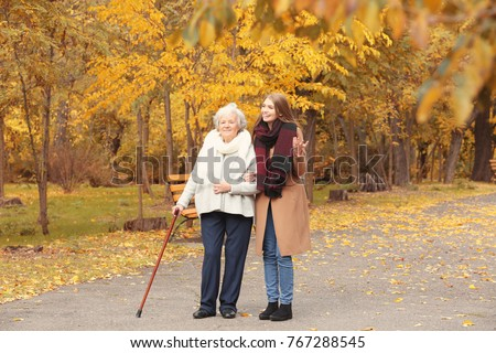 Senior woman with cane and young caregiver in park