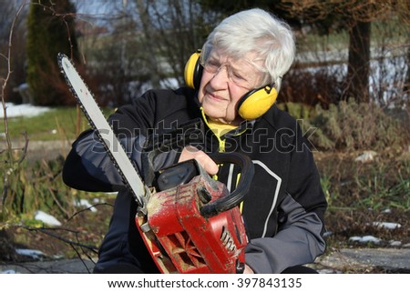 Senior woman with chainsaw - stock photo
