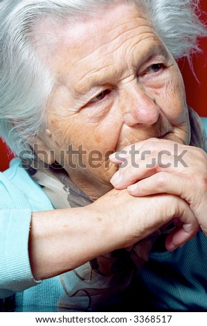 Senior woman with clasped hands looking away - stock photo