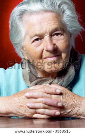 Senior woman with clasped hands looks at the camera - stock photo