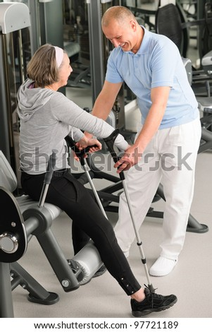 Senior woman with crutches getting help of physiotherapist at gym - stock photo