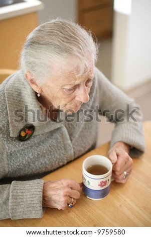 Senior woman with cup of tea at home. Shallow DOF. - stock photo