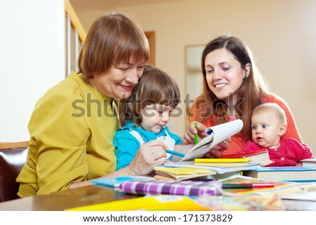 Senior woman with daughter and grandchildren drawing on paper at home. Focus on mature - stock photo