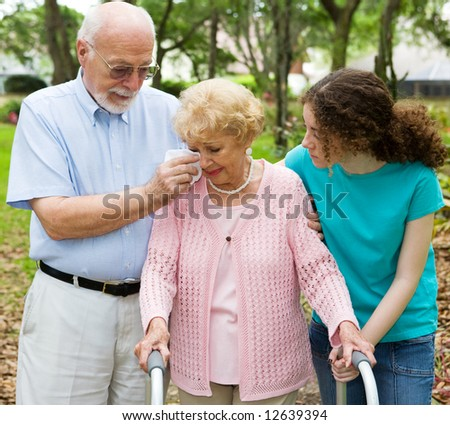 Senior woman with disability crying as her husband and granddaughter comfort her. - stock photo